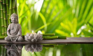 Buddha in meditation with burning candle
