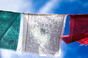 Colorful (green, white, red) Tibetan Buddhist prayer flags fluttering against a cloudy blue sky (close-up).